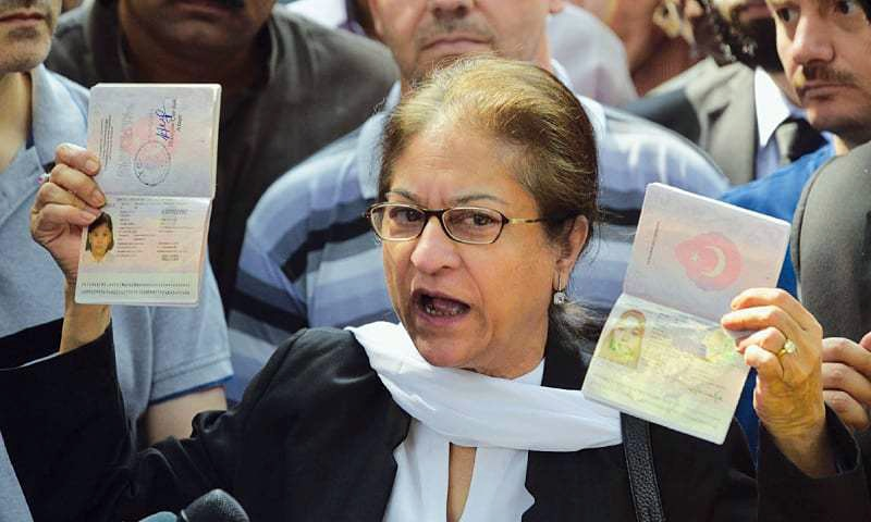 Asma Jahangir in Oct 2017 holds up the passports of a missing Turkish couple who were said to have been deported from Pakistan. ─ Dawn/File