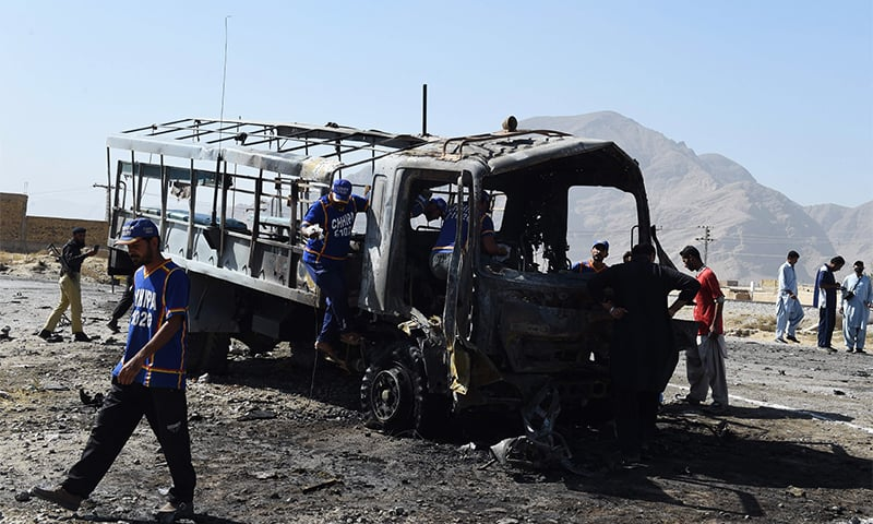 Investigators examine the burnt police truck after the blast. ─ AFP