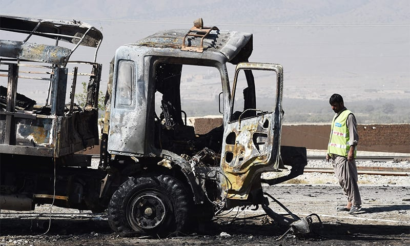 Investigators collect evidence from a burnt police truck after a blast on the outskirts of Quetta. ─ AFP