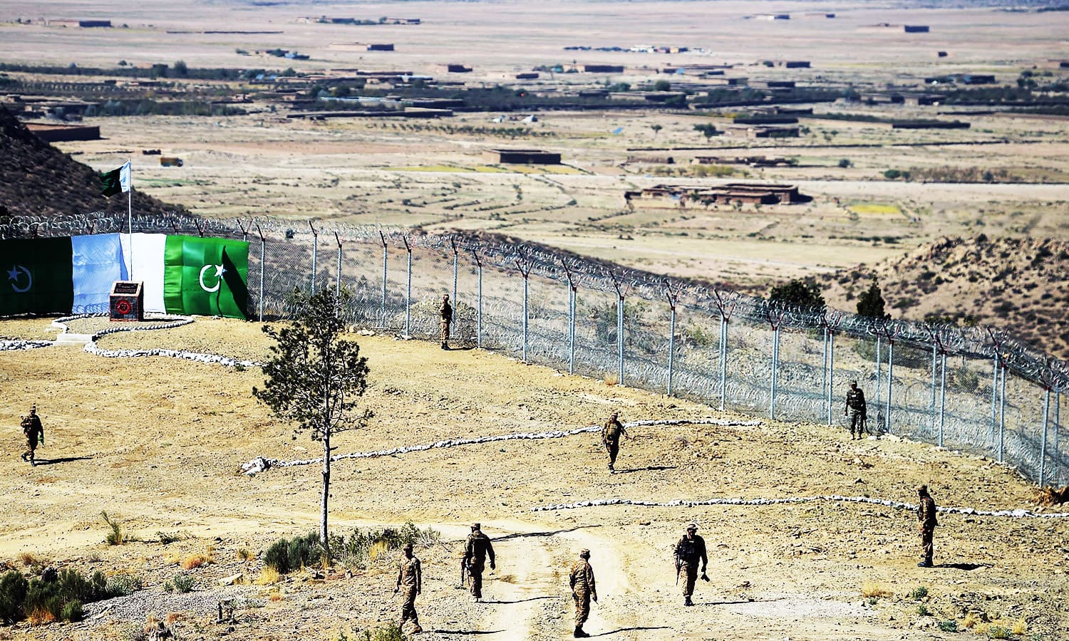 Soldiers patrol next to a newly fenced border fencing along with Afghanistan's border. —AFP