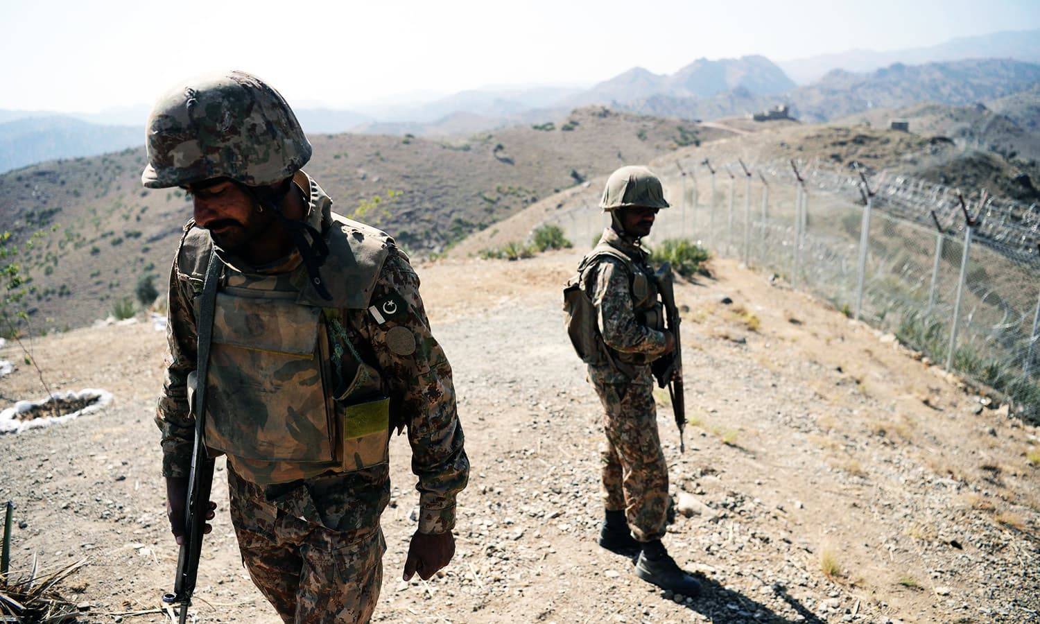 Soldiers patrol next to a newly fenced border fencing along Afghan border at Kitton Orchard Post in NW.—AFP
