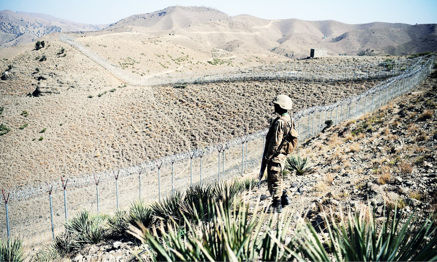 A Pakistani soldier keeps vigil next to a newly fenced border fencing at Kitton Orchard Post in NW.—AFP