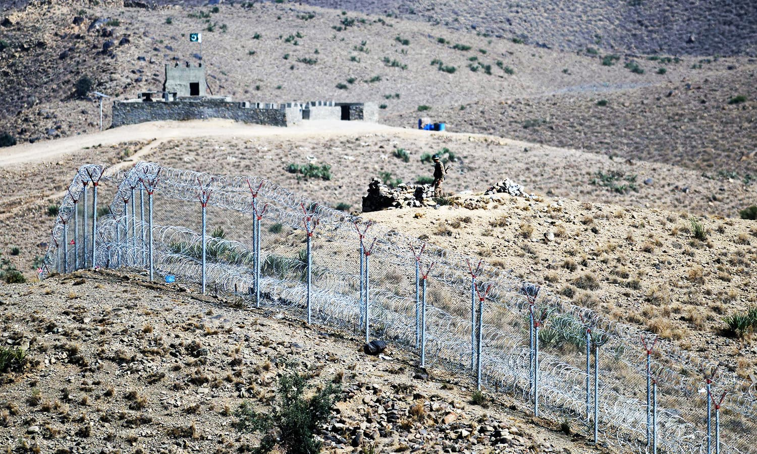 A soldier keeps vigil beside a newly fenced border fencing along Afghan border at Kitton Orchard Post in NW.—AFP