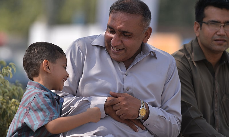 Khalil plays with his son at the site of the attack in Lahore. ─ AFP