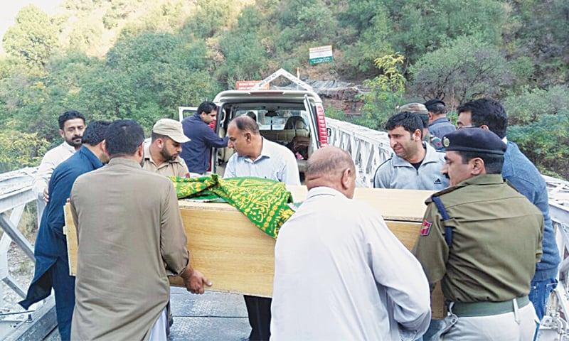 Relatives and officials from both sides of the Line of Control transfer the coffin of Salima Begum to an ambulance on the Kaman Bridge at the Chakothi-Uri crossing point.—Dawn