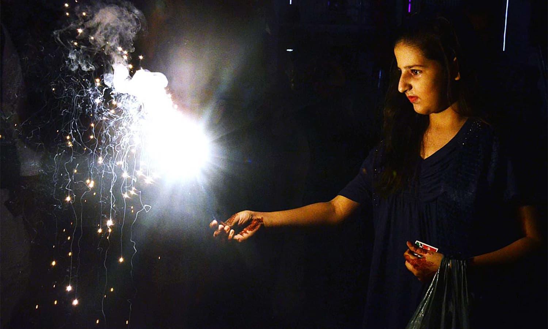 A woman belonging to Karachi's Hindu community plays with fireworks. ─ APP