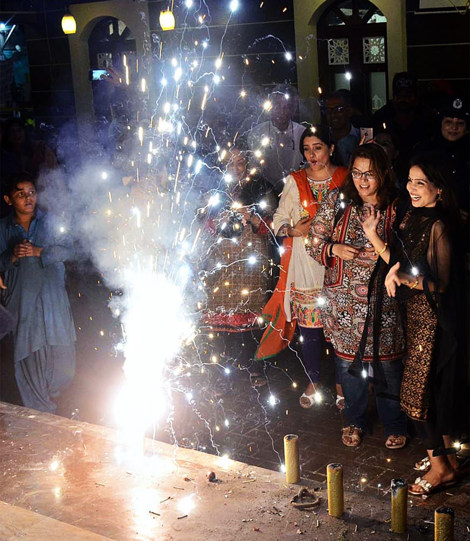 Women belonging to the Hindu community watch a firework display during Diwali celebrations at the Hindu Colony Swaminarayan Mandir. ─ APP