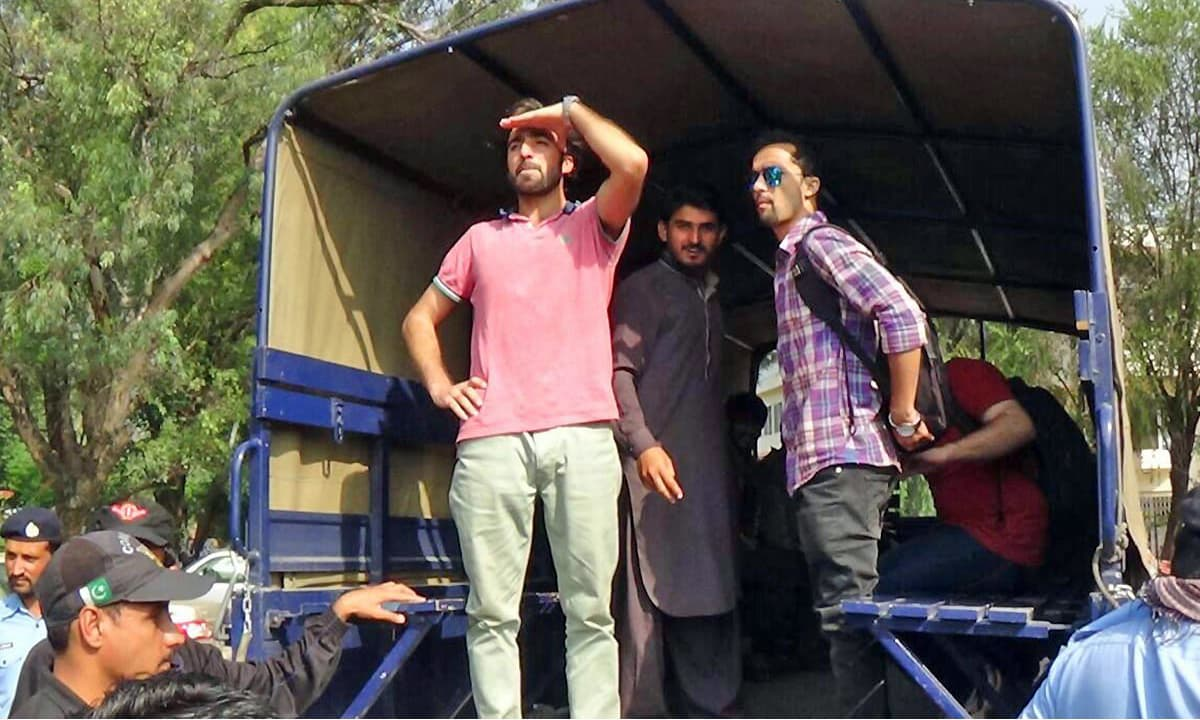 QAU students standing inside a police van after being arrested during a protest. —Online