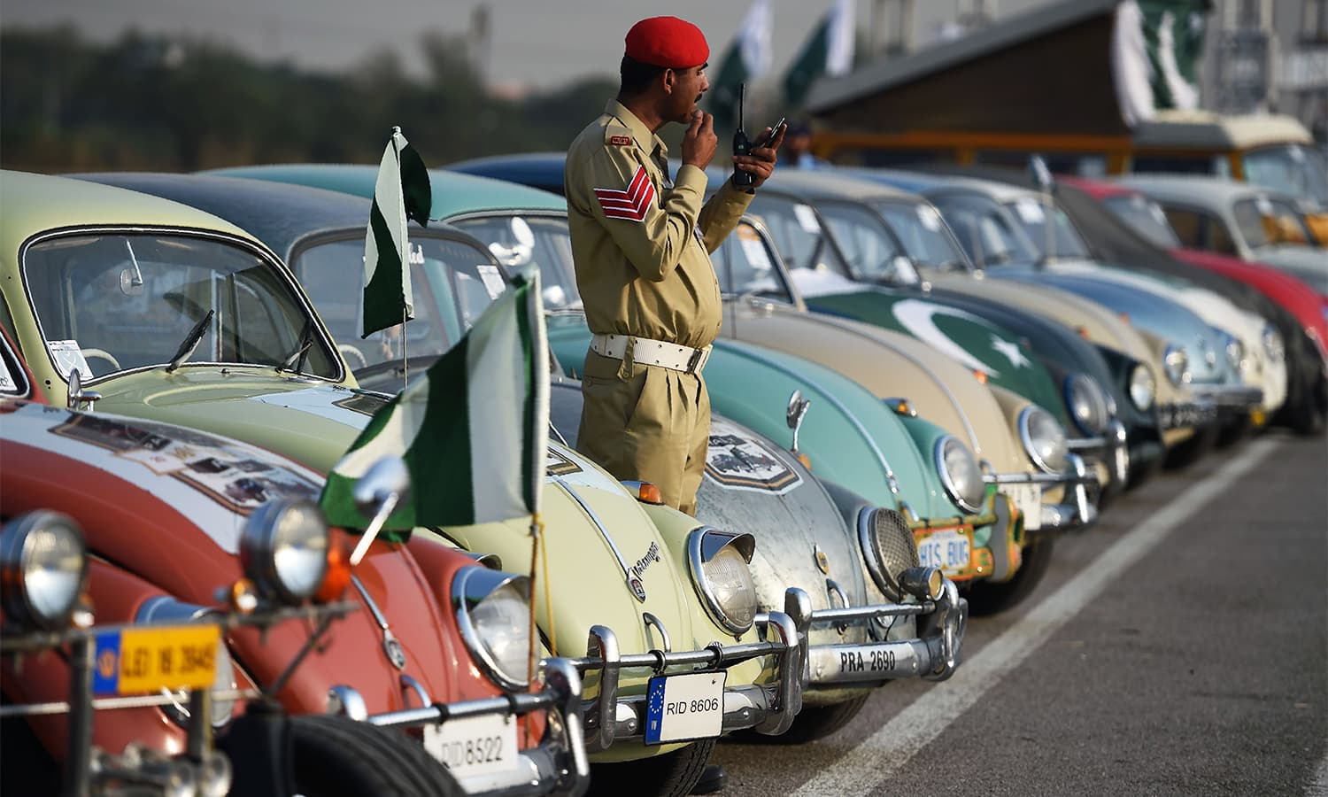 A Pakistan Army personnel looks at his moustache in a mirror next to vintage cars at the end of Motor Rally in Islamabad on October 23.— AFP
