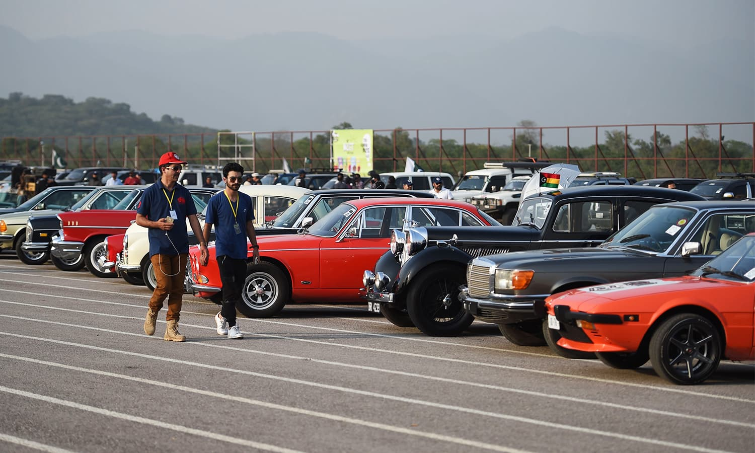 Participants walk past cars at the end of Motor Rally in Islamabad.— AFP