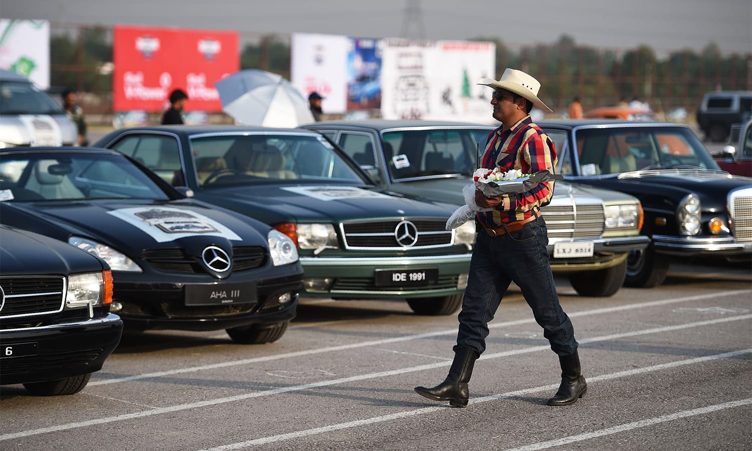 A participant walks past vintage cars at the end of Motor Rally in Islamabad.— AFP