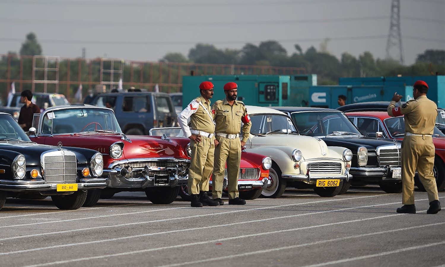 Pakistani Army personnel pose for a picture in front of vintage cars at the end of Motor Rally in Islamabad.— AFP