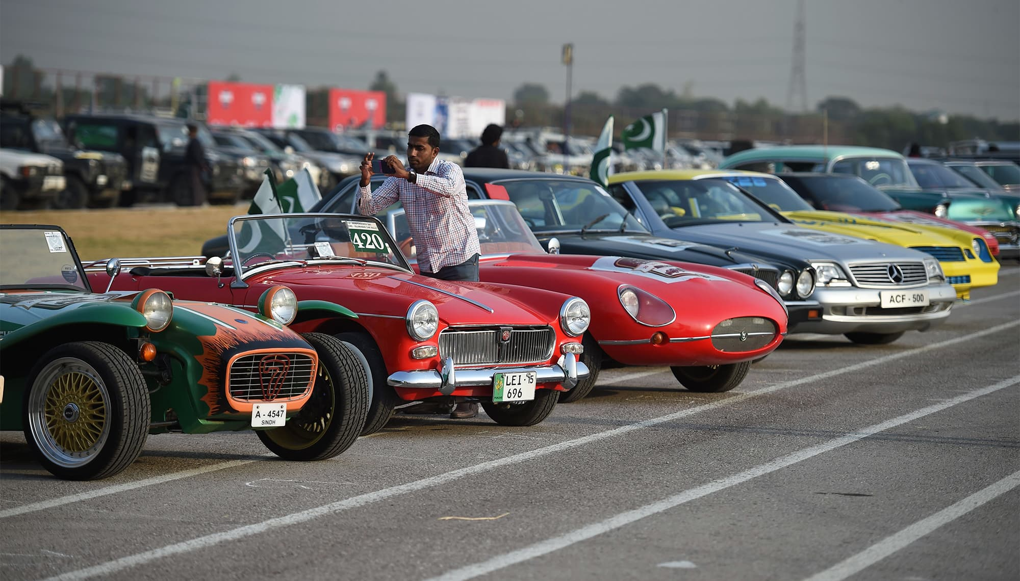 A Pakistani man takes pictures of vintage cars at the end of Motor Rally in Islamabad on October 23, 2017.  The rally which is organised by Pakistan's army gathered different vehicles from 23 different motor clubs across Pakistan. / AFP PHOTO / FAROOQ NAEEM — AFP or licensors