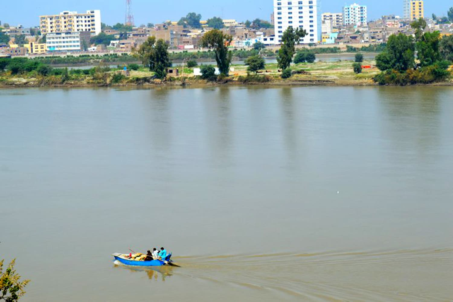 A boat floating on the Indus. Rohri can be seen in the background.