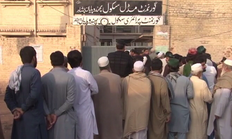 Voters line up outside a polling station.— DawnNews