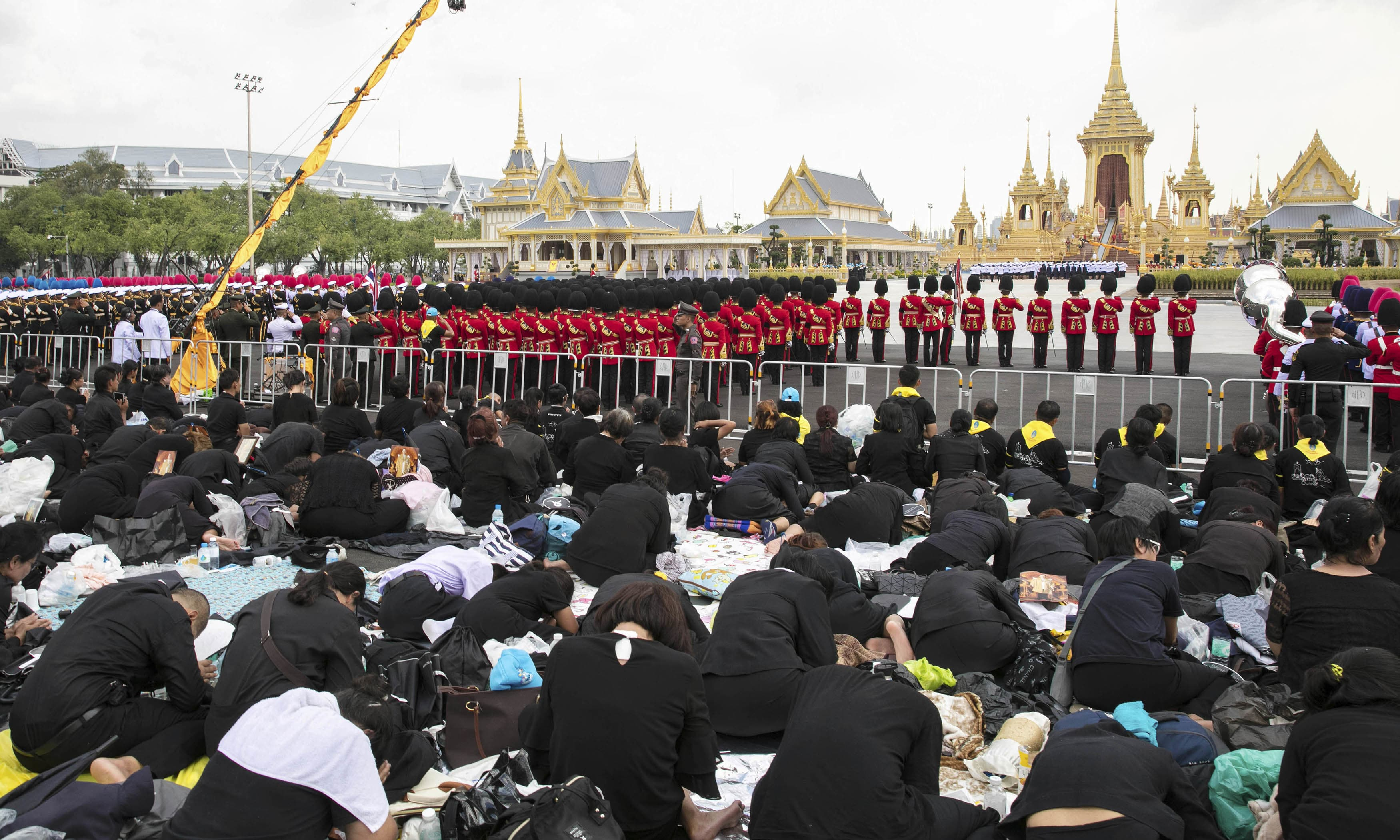Thai mourners pray during the funeral procession and royal cremation ceremony of late Thai King Bhumibol Adulyadej. —AP