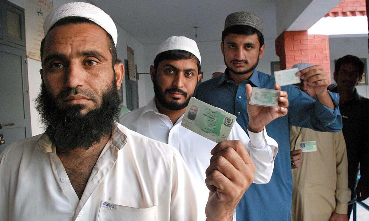 Voters showing their CNIC while standing in queue at polling station during by-election in NA-4 constituency. —APP