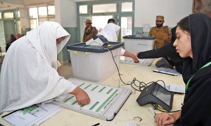 A woman uses an electronic machine, being tested for the first time, to cast her vote in NA-4 by-election in Peshawar on Thursday. — Photo by Abdul Majeed Goraya