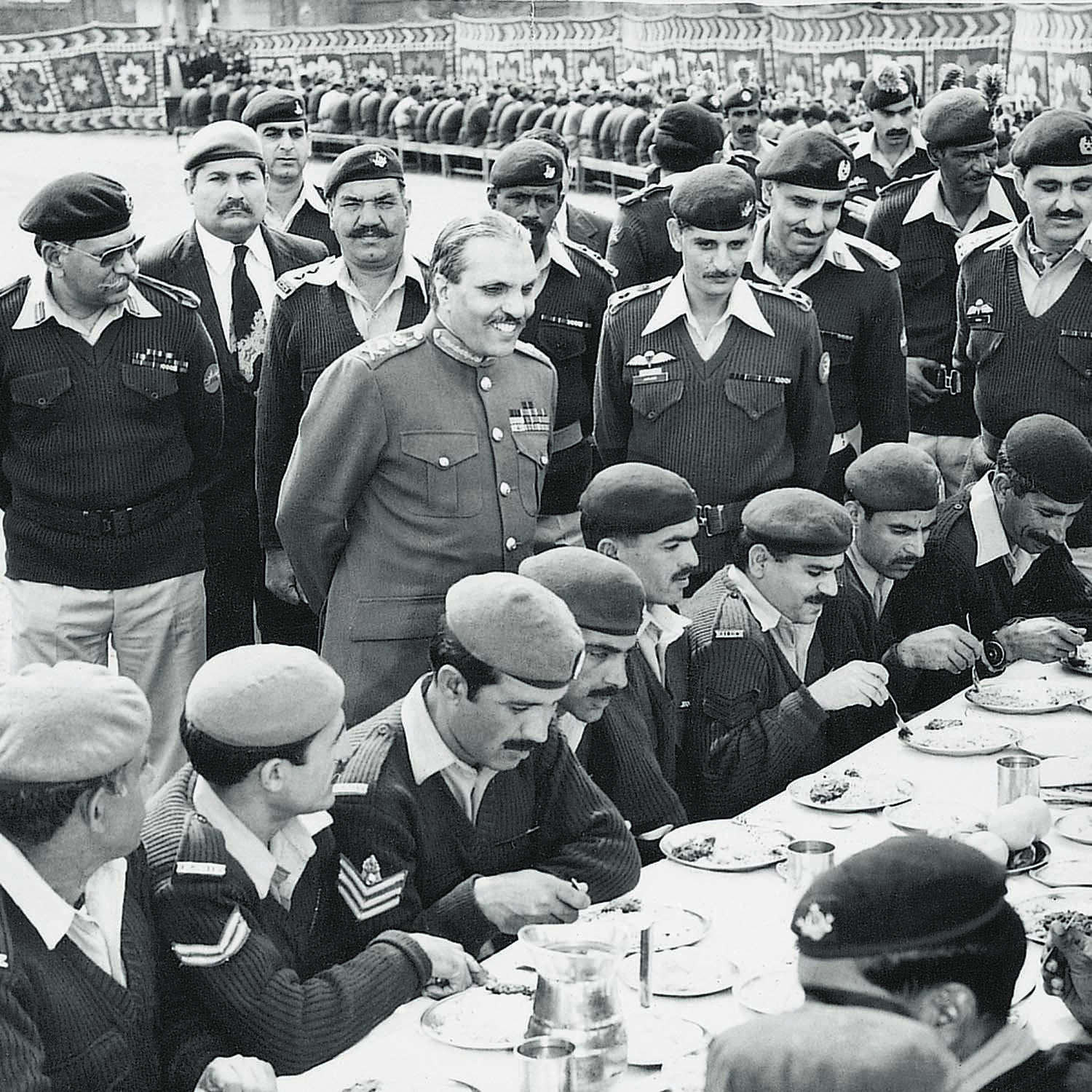 GENERAL Ziaul Haq, flanked by senior officers, is seen smiling at the traditional soldiers' feast held at the Army barracks. At least in public, Zia was all smiles all the times. | Photo: Dawn / White Star Archives