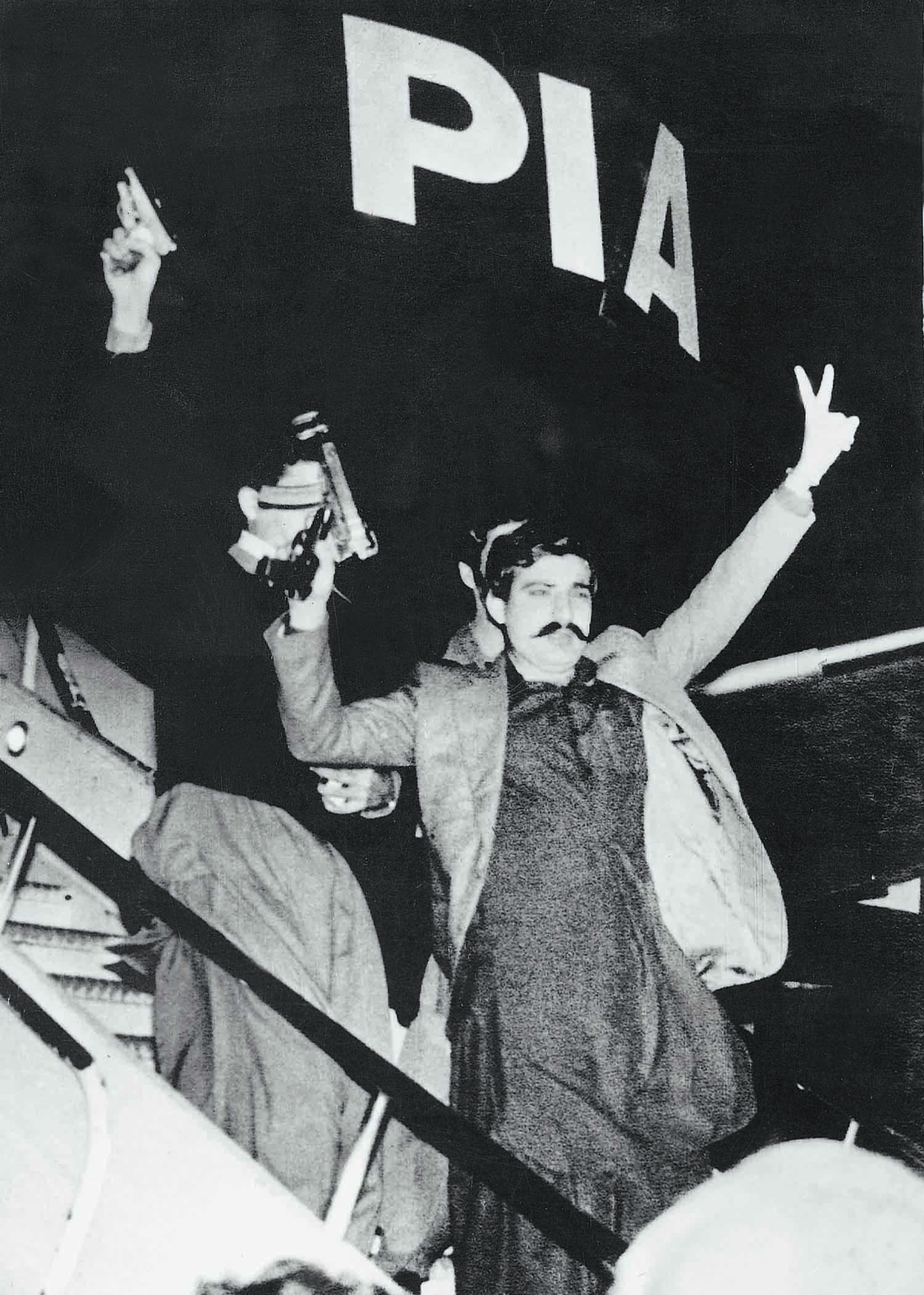 Al-Zulfikar activist Salamullah Tipu, alias Alamgir, waving arms and flashing a 'V' sign at Damascus Airport in Syria, leaving the PIA plane that he and his colleagues had hijacked while it was on its way from Karachi to Peshawar in March 1981. | Photo: Dawn / White Star Archives