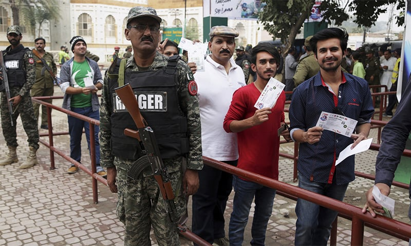 Soldiers stand guard next to cricket fans arriving to watch 3rd T20I match. ─AP