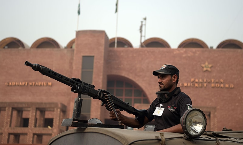 A policeman stands guard outside Gaddafi Cricket Stadium. ─AFP