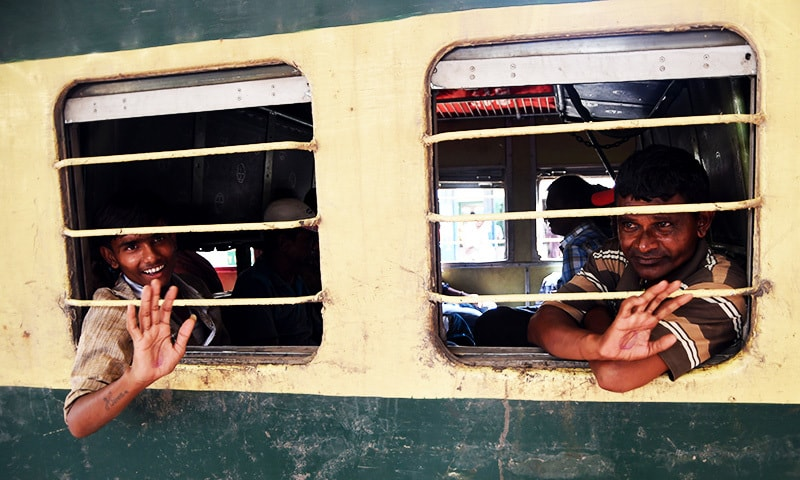 Indian fishermen released from Malir jail wave from train at a railway station in Karachi.—AFP