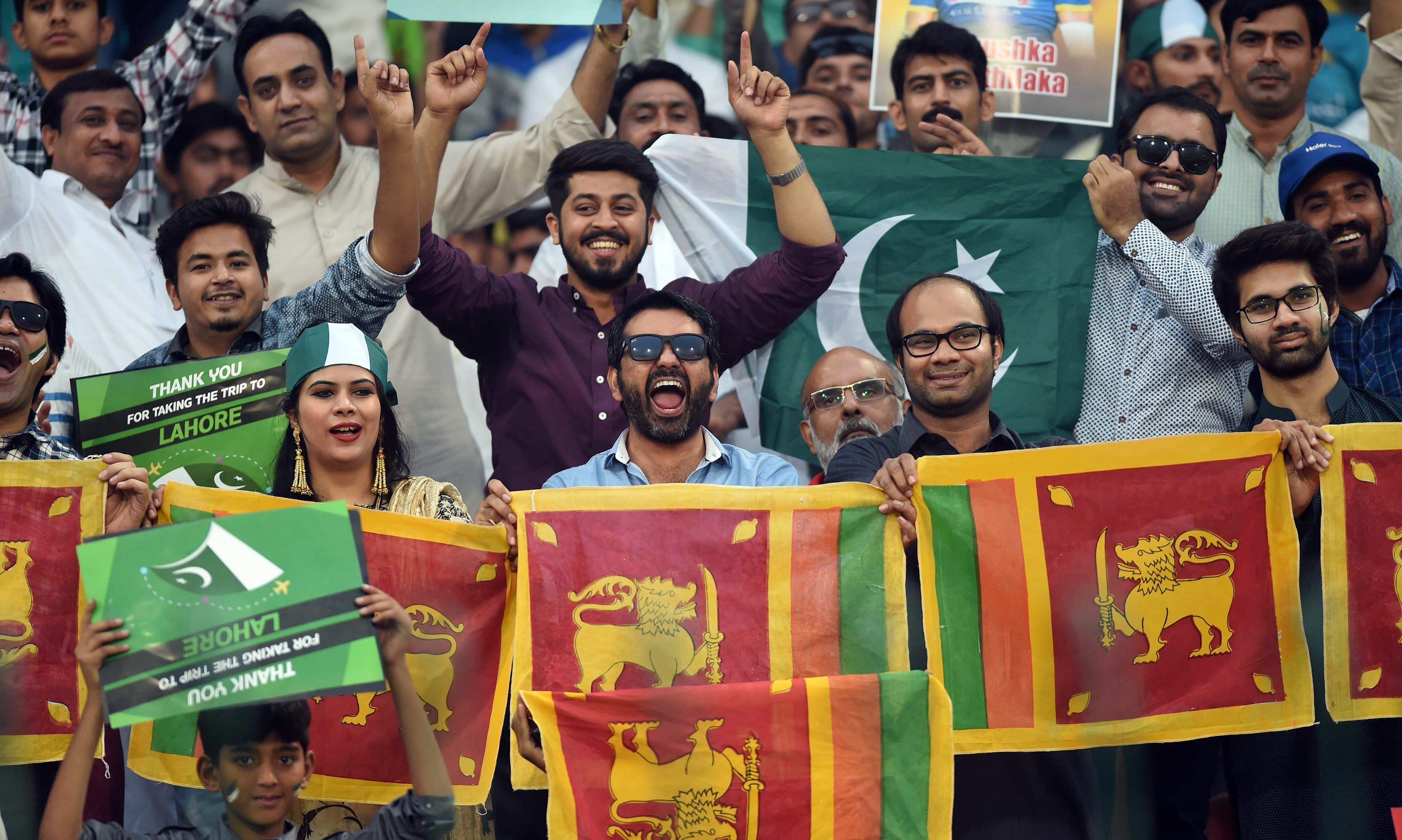 Spectators hold Sri Lanka's national flag during the T20 cricket match. —AFP