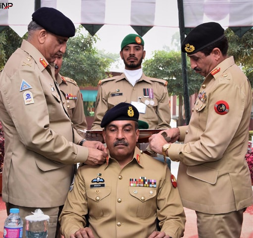 Chief of the Army Staff Gen Qamar Javed Bajwa and another army officer place the rank of Colonel Commandant of Mujahid Force on the shoulder epaulettes of Lt Gen Nadeem Raza on Monday.—INP