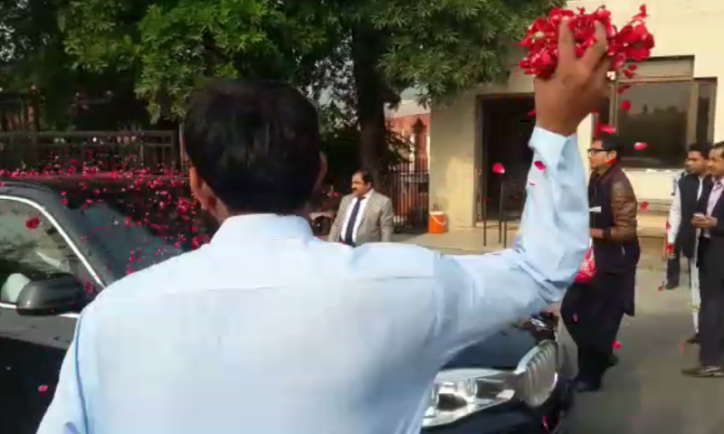 A supporter showers rose petals on the car carrying Nawaz Sharif to Punjab House.— DawnNews