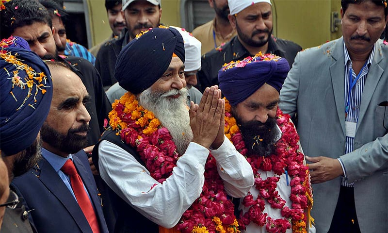 Sikh devotees return the welcome gesture on their arrival at Wagah border. — APP