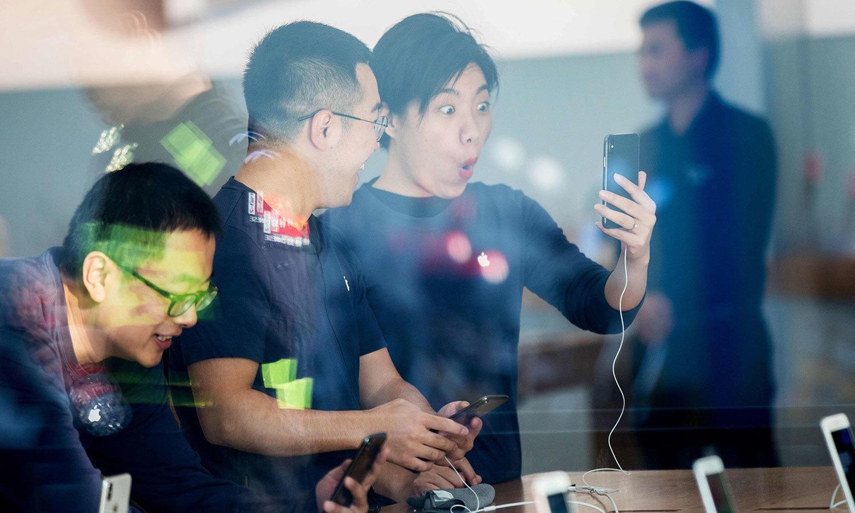 چینی شہر ہینگ زو میں آئی فون ایکس خریدنے پر صارف کا اظہار — اے ایف پی فوٹو