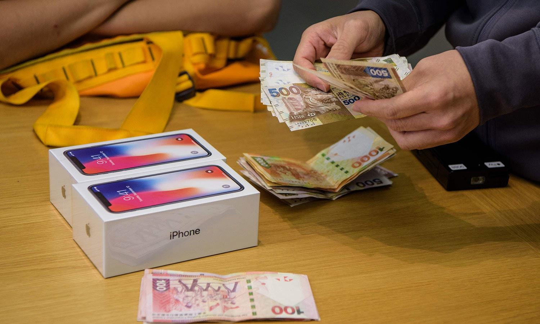 ہانگ کانگ میں ایپل اسٹور کا عملہ ایک صارف کی جانب سے دو فونز خریدنے پر ادا کی گئی رقم گن رہا ہے — اے ایف پی فوٹو