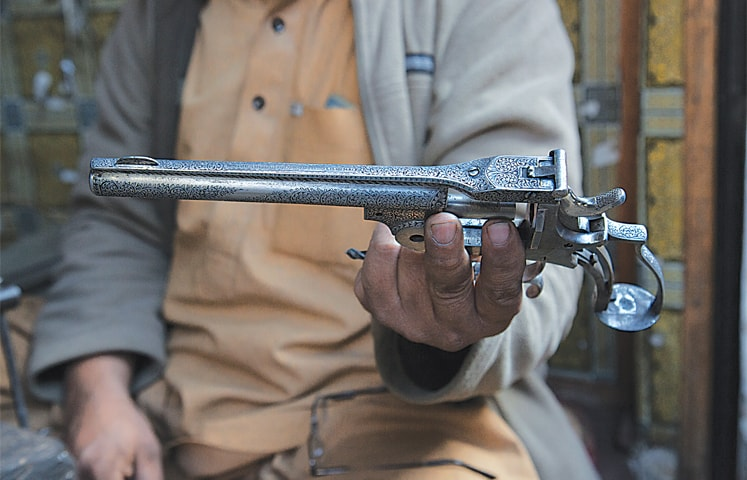 Intezar Hussain, a craftsman, shows a revolver on which he has engraved a new design