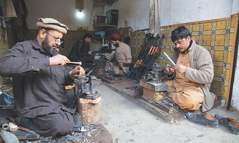 Arms manufacturers at work, creating different parts of various weapons in a workshop in Darra Adam Khel