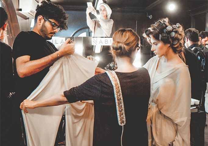 Stylist Nabila (C) and Tabesh Khoja prepare models at a fashion week | N-Pro