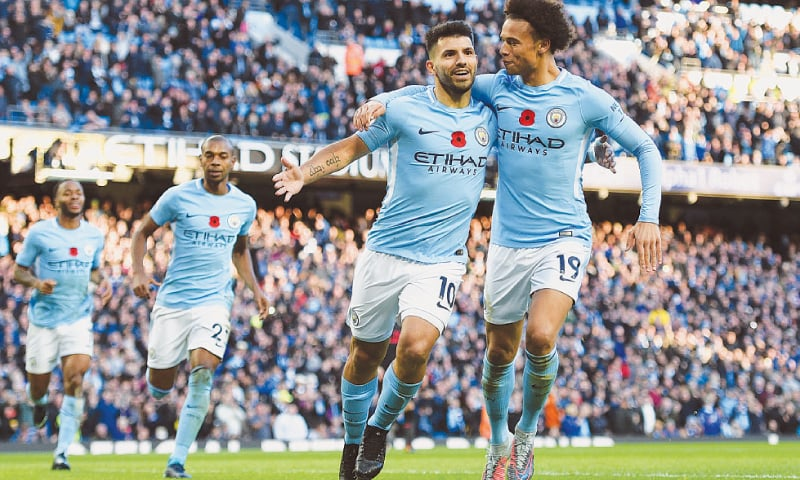 MANCHESTER: Manchester City's Sergio Aguero (second R) celebrates with team-mate Leroy Sane after scoring during the Premier League match against Arsenal at the Etihad Stadium on Sunday.—AFP
