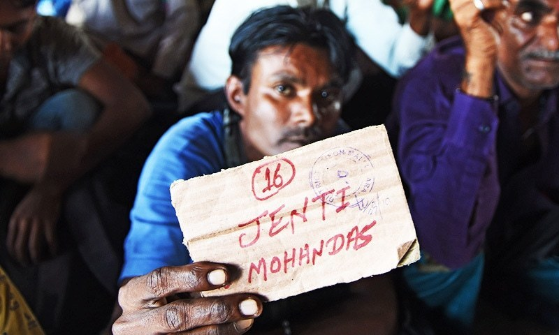 Indian fisherman released from Malir jail shows his travelling card at a railway station in Karachi. -AFP