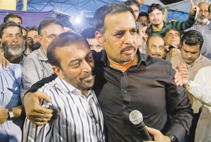 PAK Sarzameen Party leader Mustafa Kamal hugs Muttahida Qaumi Movement-Pakistan chief Dr Farooq Sattar during the joint news conference at the Karachi Press Club on Wednesday.—INP