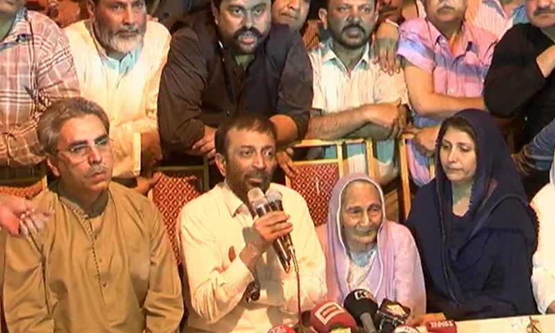 Farooq Sattar talks to media with his elderly mother sitting next to him. —DawnNews