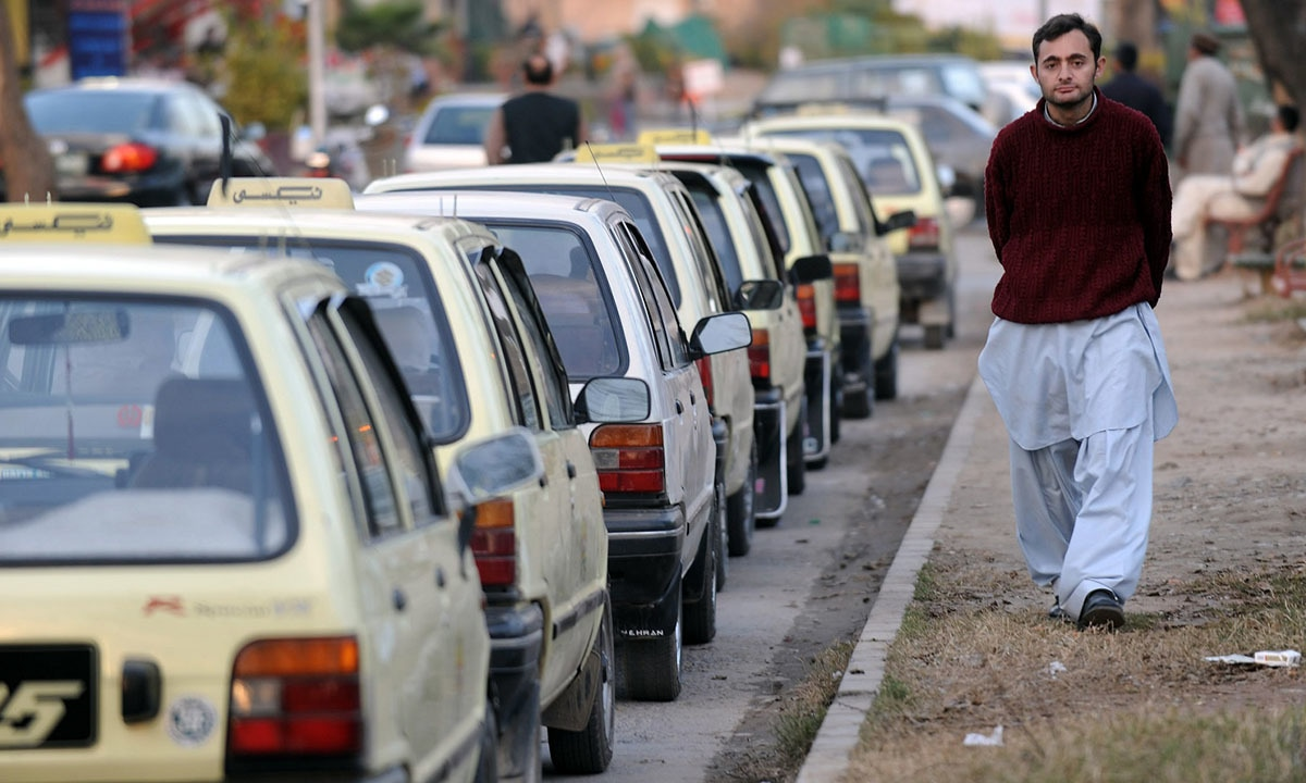 A driver waits for customers at a taxi stand outside a supermarket in Islamabad | AFP