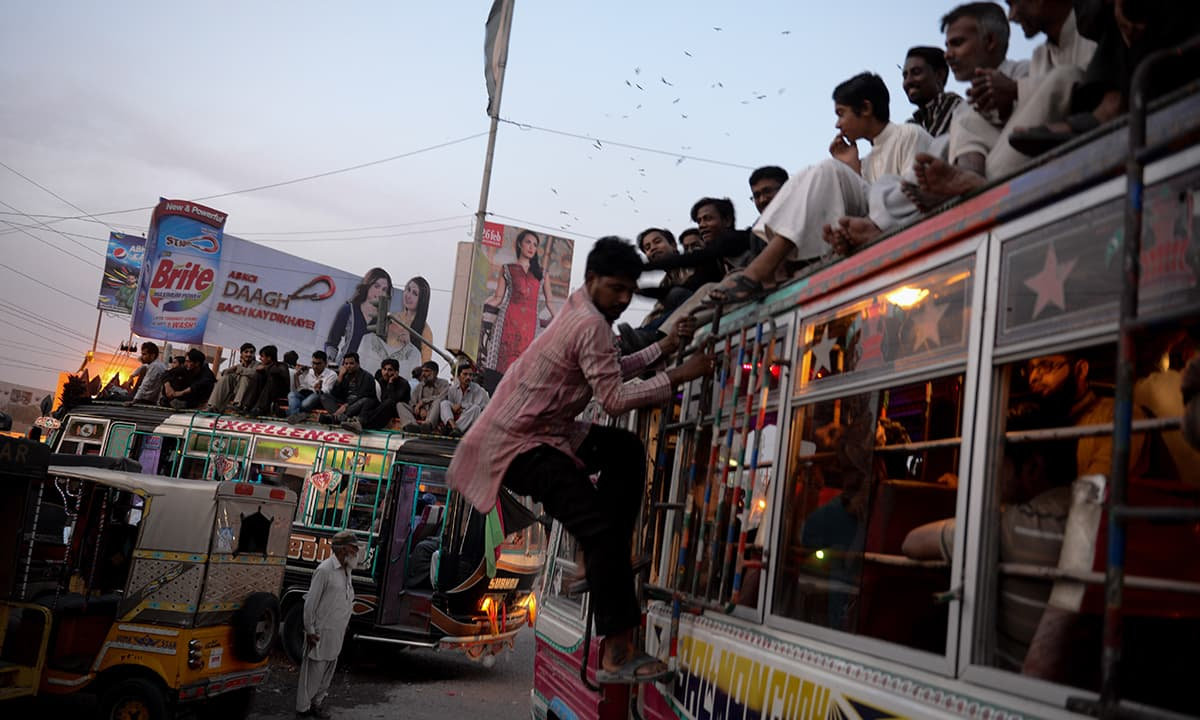 Commuters climb on to buses during rush hour in Karachi | Tahir Jamal, White Star