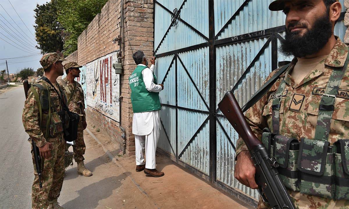 An enumerator, escorted by security personnel, marks a house during the census in Khyber Pakhtunkhwa   Abdul Majeed Goraya, White Star