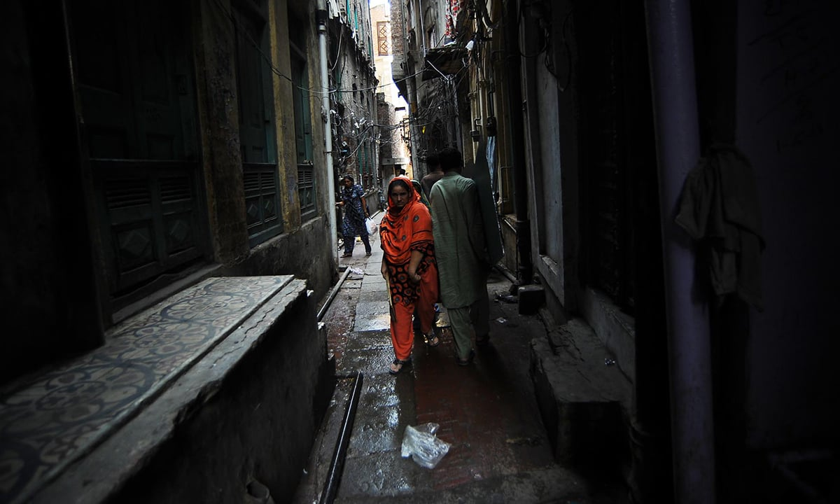 A woman walks through a congested alley in old Lahore | M Arif, White Star
