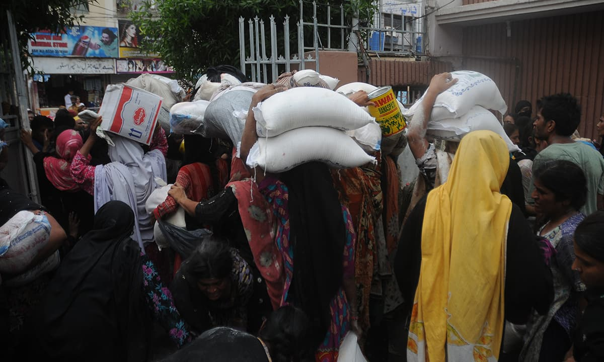 Women carrying bags of ration in Karachi | Faysal Mujeeb, White Star