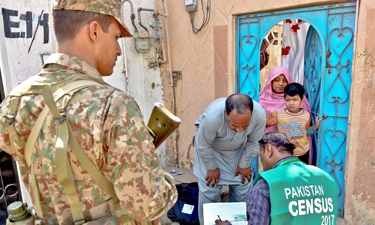 A census enumerator flanked by security personnel collects data in Karachi   Fahim Siddiqui, White Star