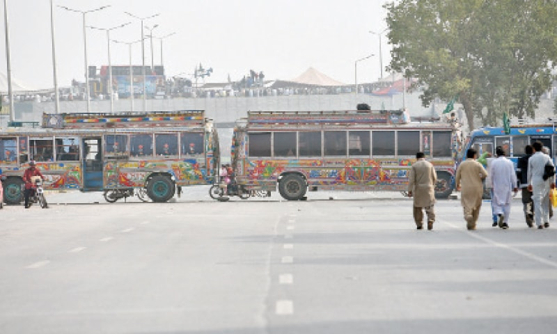 Buses have been parked to block Islamabad Expressway in front of the protest camp at Faizabad Interchange on Friday. — Photo by Tanveer Shahzad