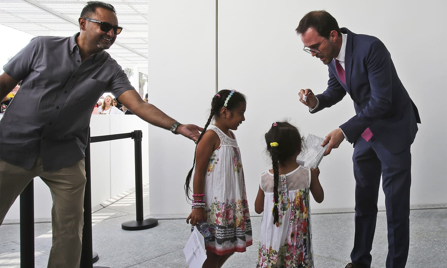 The president-director of the Louvre Museum, Jean-Luc Martinez, right, gives gifts to the two daughters of a family for being the first visitors at the Louvre Museum in Abu Dhabi. — AP