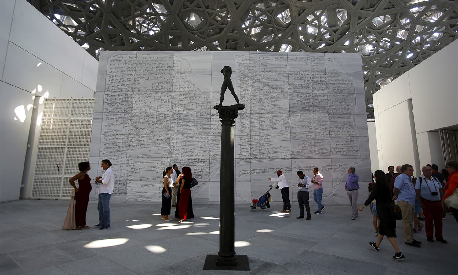 "Visitors stand near the bronze sculpture, ""Walking Man, On a Column"" of Auguste Rodin, created in 2006 by Fonderie Coubertin, during the public opening day of the Louvre Museum, in Abu Dhabi. — AP"