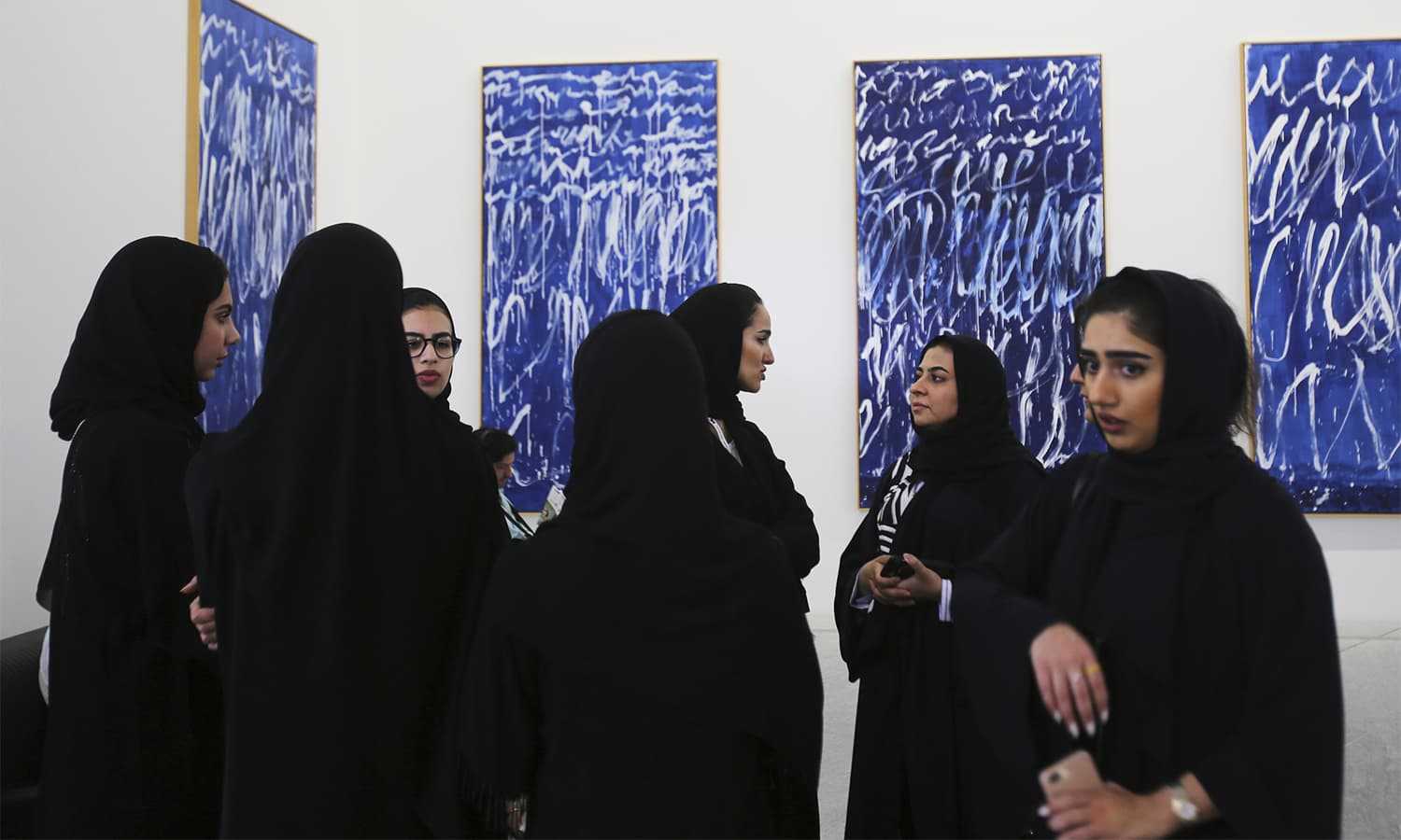 "Emirati women stand in front of a series of nine panels titled ""Untitled I-IX"" by American painter Cy Twombly, during the public opening day, in Abu Dhabi. — AP"